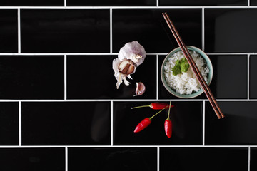 Asian rice dish and ingredietns on black railway tiles