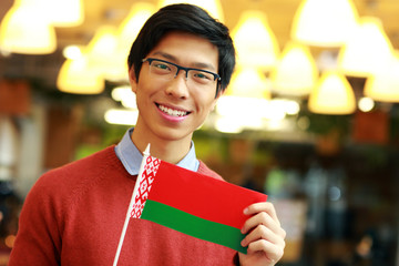 Happy young asian boy holding flag of Belarus