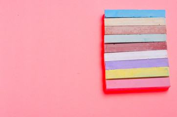 colored chalks for drawing on a pink sheet