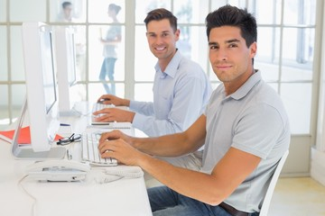 Casual businessmen smiling at camera at desk