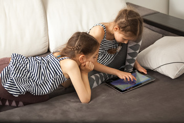 sisters with tablet on couch at home