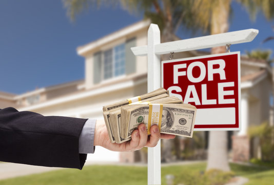 Buyer Handing Over Cash for House with For Sale Sign