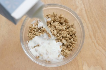 Prepairing healthy breakfast, pouring low fat yogurt