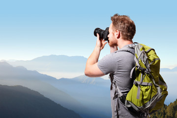 Young man taking photo on top of mountain