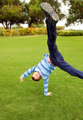Beautiful child playing on green grass in a park jumping