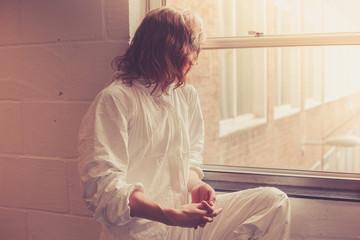 Woman in boiler suit by window