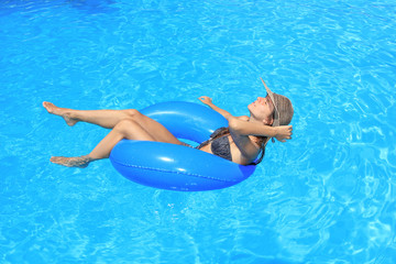 Young woman relaxing at the swimming pool