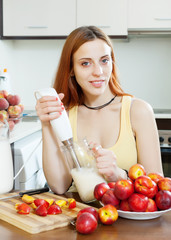 woman cooking beverages  from nectarines and milk at  kitchen