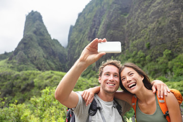 Couple taking selfie with smartphone hiking Hawaii