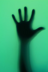Hand silhouette on green glass