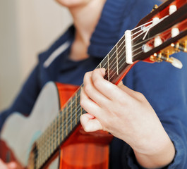 woman plays on modern acoustic guitar