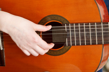 female hand plays on acoustic guitar
