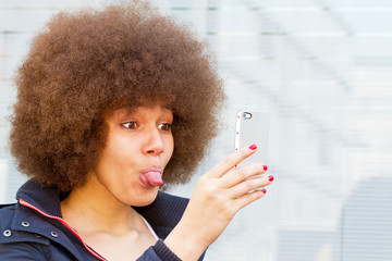 Young woman with afro haircut taking a funny selfie