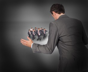 Composite image of businessman posing with hands out with tiny b