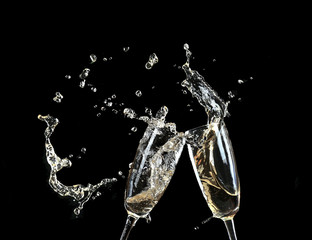 Glasses of champagne with splash, on black background