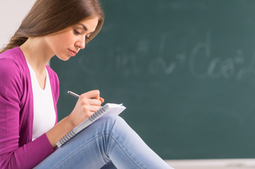adult student girl sitting and writing.