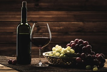 Bottle of red wine, glass and grape in basket in wooden interior