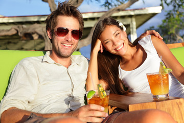 Fotobehang - Couple drinking alcohol at beach club having fun