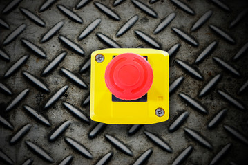 Emergency stop button pushing stop button on diamond steel backg