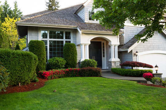 Clean exterior home with lush green grass yard, trees in bloom, and flowering bushes during spring time season