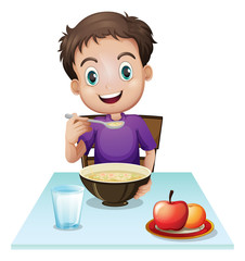 A boy eating his breakfast at the table