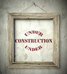 Under construction emblem in old wooden frame