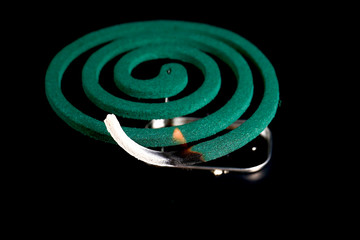 Closeup of mosquito coil smoking on black background