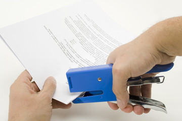 Stapling a document / Stapler and a stack of papers.