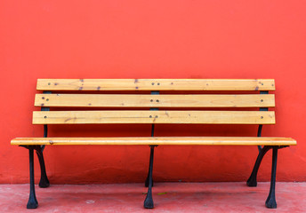 wooden long bench against blank red wall