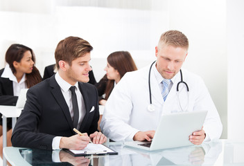 Doctor And Businessman Discussing Over Laptop