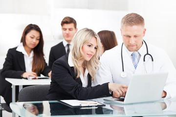 Male Doctor And Businesswoman With Laptop