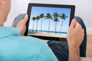 Man Looking At Beach Photo On Tablet