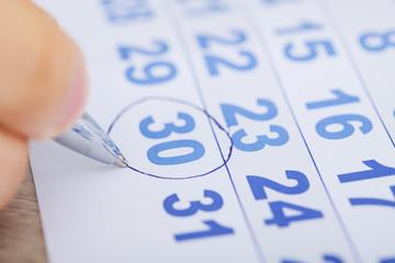 Fototapete - Businessman Marking Date On Calendar At Desk