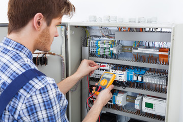 Technician Examining Fusebox With Insulation Resistance Tester