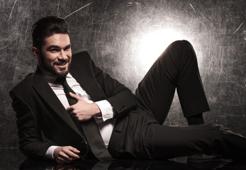 business man in suit holding his tie and smile