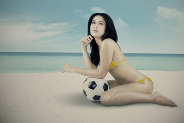 A model with soccer ball at beach