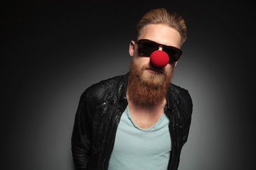 young bearded man wears a red nose