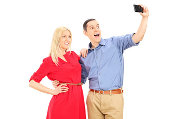 Young man and woman taking selfie with cell phone