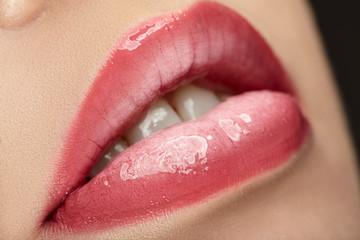 Beautiful female with pink shiny lips close up