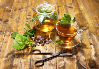 Composition of fresh mint tea in glass cup and teapot