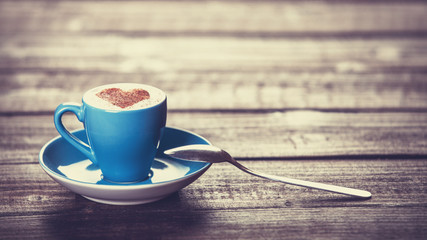Cup of coffee with shape heart on a wooden table.