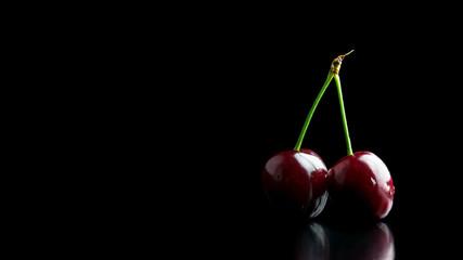Two ripe red cherries