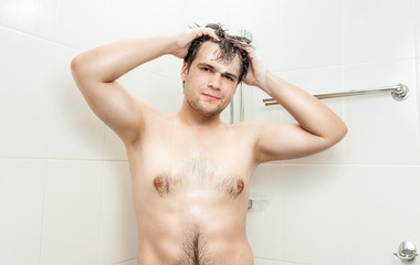 young man with muscular chest washing head at shower