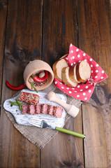 Composition of knife,    sliced salami sausage with sesame,