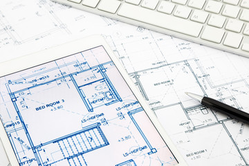 house blueprints and floor plan with tablet