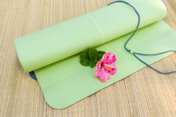 A yoga mat rolled out halfway with a flower laying on it.