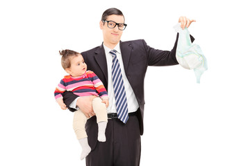 Young father holding a baby and a dirty diaper