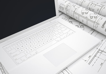 Scrolls of architectural drawings and laptop