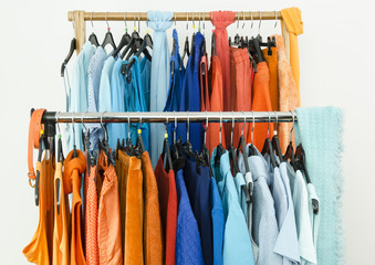 Closeup on complementary color blue and orange clothes on a rack