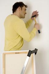 Junger Mann Aufhängen Malerei,stehend auf Leiter